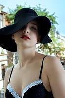 sensual beautiful woman in a fashion shot wearing a black hat and bra outside of the window with old urban background in summer day