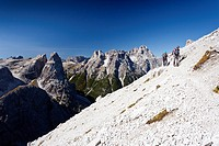 Hikers ascending the Alpinisteig Climbing Route, overlooking the Einser and Dreischusterspitze mountains, with the Val Fiscalina valley below, Sexten,...