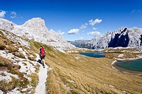 Hiker at the Boedenseen lakes while descending from Three Peaks Hut, Schusterplatte Mountain on the left, Einser Mountain on the right, Croda Rossa di...