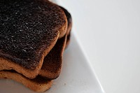 Stack of burnt toast.Several slices of burned toast stacked on a white plate