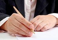 Business woman at her office signing a contract on white paper