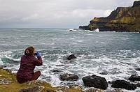 A tourist taking photos near Giant´s Causeway..