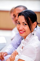 Smiling latin business woman looking at camera with satisfaction and working colleagues in office