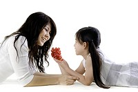 Mother and daughter sharing grapes on white background