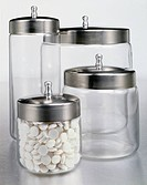 Glass storage jars with stainless steel lids.Studio shot on silver background of glass containers
