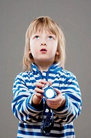 boy with long blond hair playing with flashlight