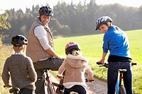 Young parents with children ride bikes in park
