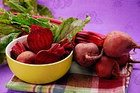 fresh beets with leaves on purple background