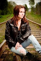 a beautiful model posing on the railroad tracks