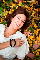 A portrait of a happy beautiful caucasian woman lying down on autumn leaves on the ground