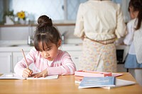 Girl doing homework at kitchen table