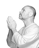 Senior man praying on white background in high key format