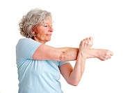 Elderly woman stretching her arms while doing fitness exercises