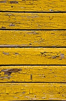 Ancient yellow painted wooden wall with peeling paint background.