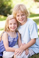 Brother and sister pose in a park