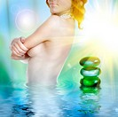 sexy young woman in water with spa stones
