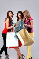 a colorful studio image of three beautiful young women standing, holding shopping bags and looking very happy, smiling, admiring a dress