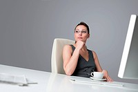 Successful business woman at office having cup of coffee sitting at computer desk