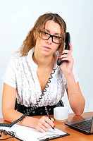Cute businesswoman talking phone in the office