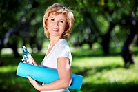 Mature woman with a gym mat and a bottle of water in the park