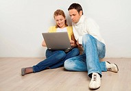 Happy young couple sitting on the floor with laptop computer