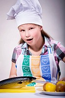a girl cooking fish in the kitchen