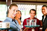 Woman as waitress in a bar or restaurant with coffee mugs, in the background are guests