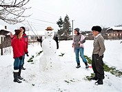 Multi generation family gathering happily together around a snowman, in winter holiday