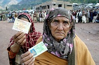 Women showing their ID cards, hoping to get also food during a distribution in Hatian, Kashmir, Pakistan On 8 october 2005, a severe earthquake hit No...
