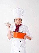 Young chef holding a pot and a wooden spoon