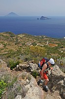 Tourist on Panarea island, volcanic island of Stromboli at back, Panarea Island, Aeolian Islands or Lipari Islands, Sicily, Southern Italy, Italy, Eur...
