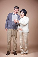 A old man and old woman looking at tablet PC