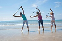 Three women doing stretching exercises with walking sticks on the beach, Camaret-sur-Mer, Finistere, Brittany, France, Europe