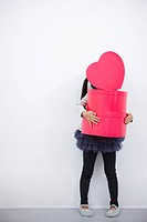 A girl holding red heart box