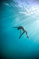 Woman Swimming Underwater In Ocean