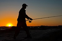 Sunset silhouette of Fisherman casting the fishing rod