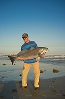 Angler at a beach presenting trophy sized fish caught in the Gulf of Mexico