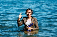 Elegant and happy wet woman in the water with a diving mask and a suit and showing ok signal