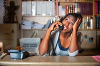 Young attractive black girl having private phone conversation while working as ofice clerk