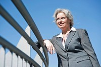 Businesswoman standing at a railing and looking into the distance