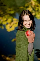 Young woman holding an apple, autumn scene