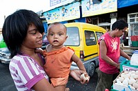 Woman with her baby, she is buying Balut, a fertilized duck embryo from a roadside vendor  Carbon Market, Cebu City, Cebu, Visayas, Philippines