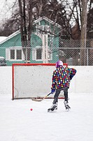 Boy playing ice hockey, on an outdoor neighborhood rink, Winnipeg, Manitoba, Canada
