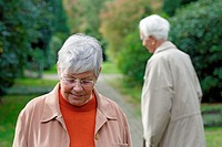 Senior caucasian woman with glasses, looking down with senior man in the background, blurred green background, Hamburg, Germany, Europe