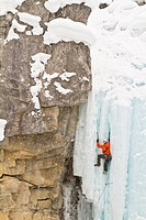 Young man ice_climbing in Banff National Park near Banff, Alberta, Canada.