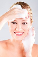 Beautiful young caucasian woman washing her face with foam