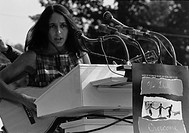 Folk Singer Joan Baez singing at the 1963 Civil Rights March on Washington. A sign hanging near the microphones reads 'We Shall Overcome.' Aug. 28, 19...