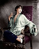 Portrait of a young woman smoking a cigarette and smiling All persons depicted are not longer living and no estate exists. Supplier warranties that th...