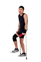 Young attractive nepalese man athlete on crutches, wearing a wrist brace and knee support, bandaged. White background. Studio shot.