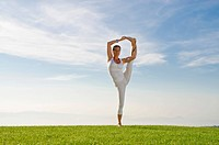 Young woman practising Hatha yoga outdoors, showing the pose utthita hasta pandangusthasana, raised hand to big toe pose, Nove Mesto, Okres Teplice, C...